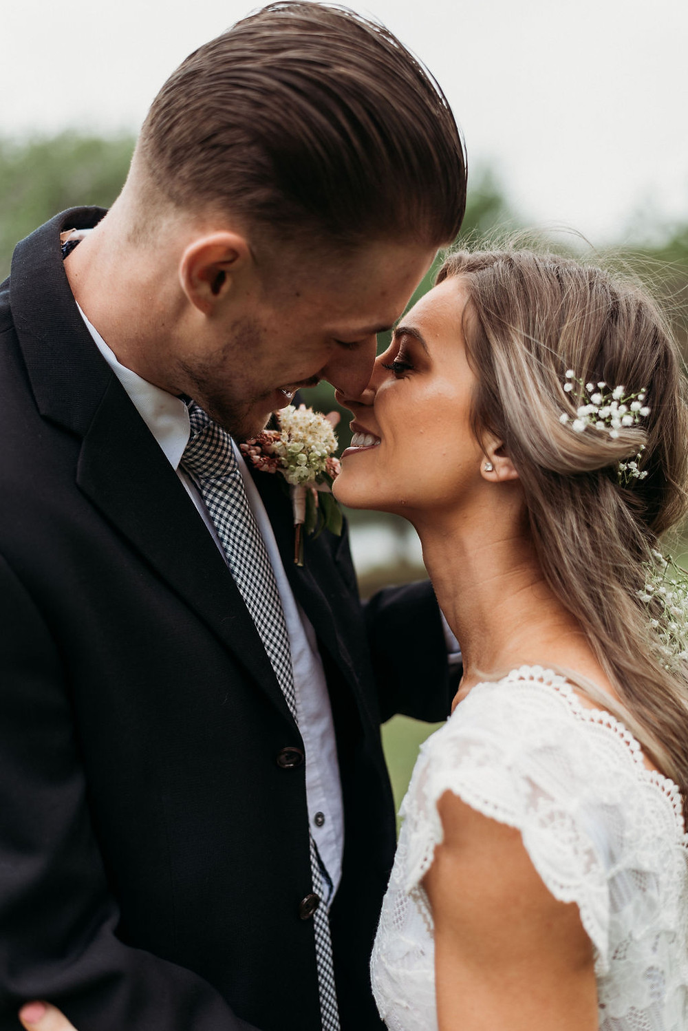 the almost kiss pose. the smile with your teeth pose. bride and groom are smiling at each other and going in for a kiss during their Austin elopement
