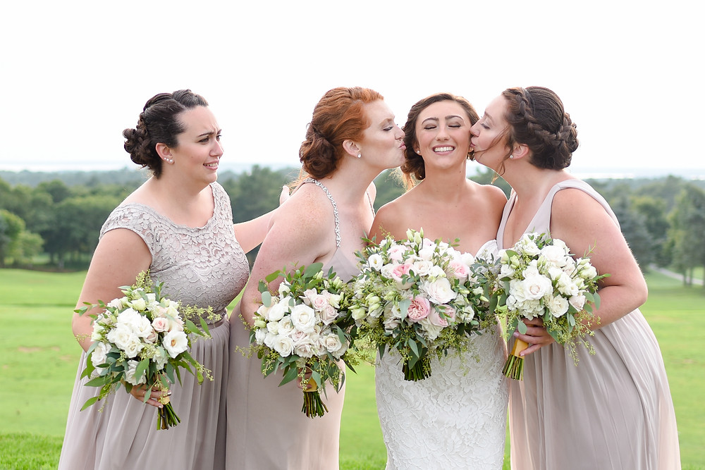 sisters kissing bride's cheeks after wedding