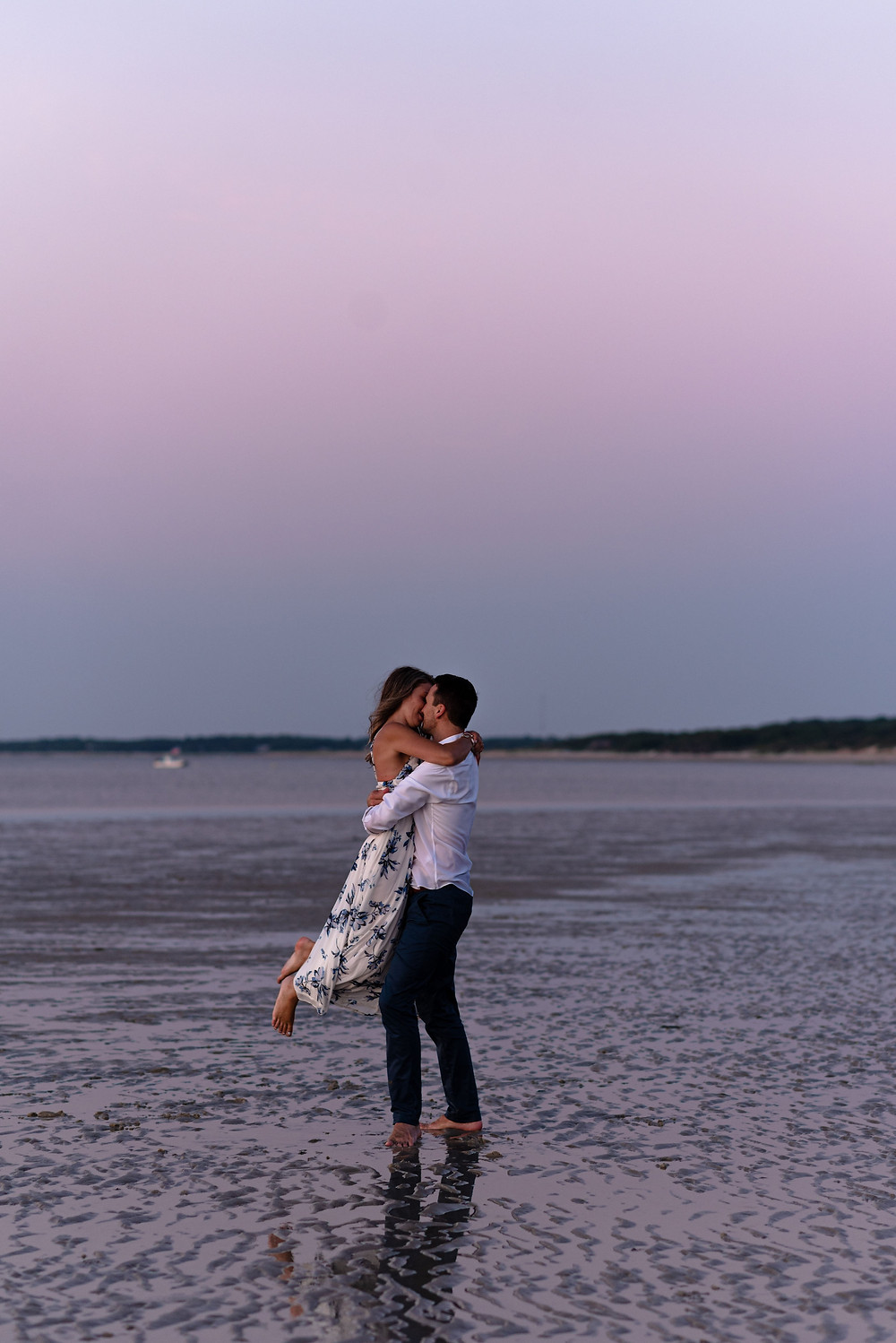 engagement session during blue hour on the beach. pink and blue skies. boy has girl in his arms, off of her feet and they're kissing