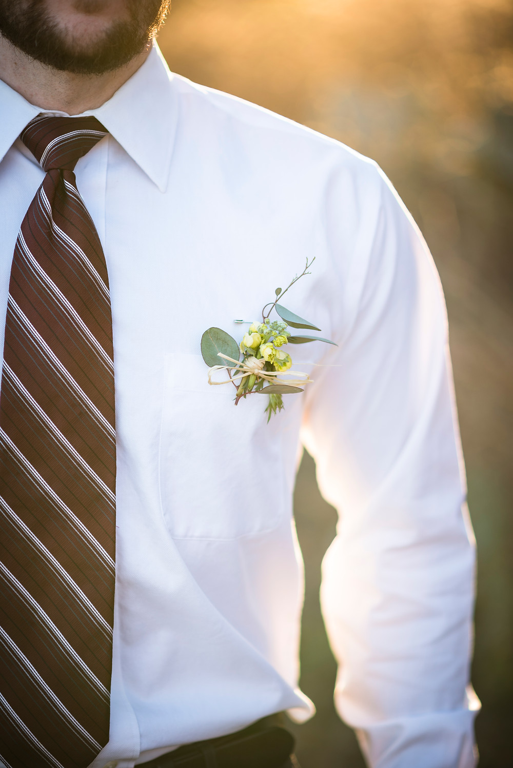a close up photo of groom's boutonniere and attire details during elopement at enchanted rock