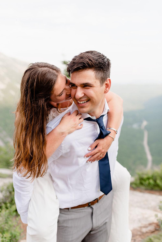 bride on groom's back kissing is cheek
