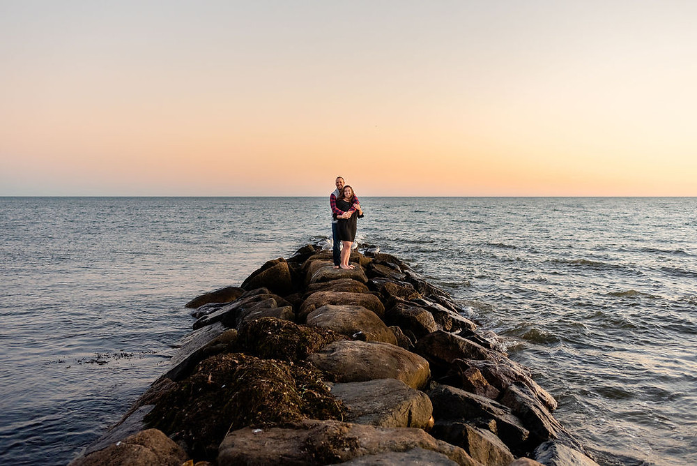 couple standing on jetty for engagement photos at lighthouse inn in West Dennis Cape cod, MA