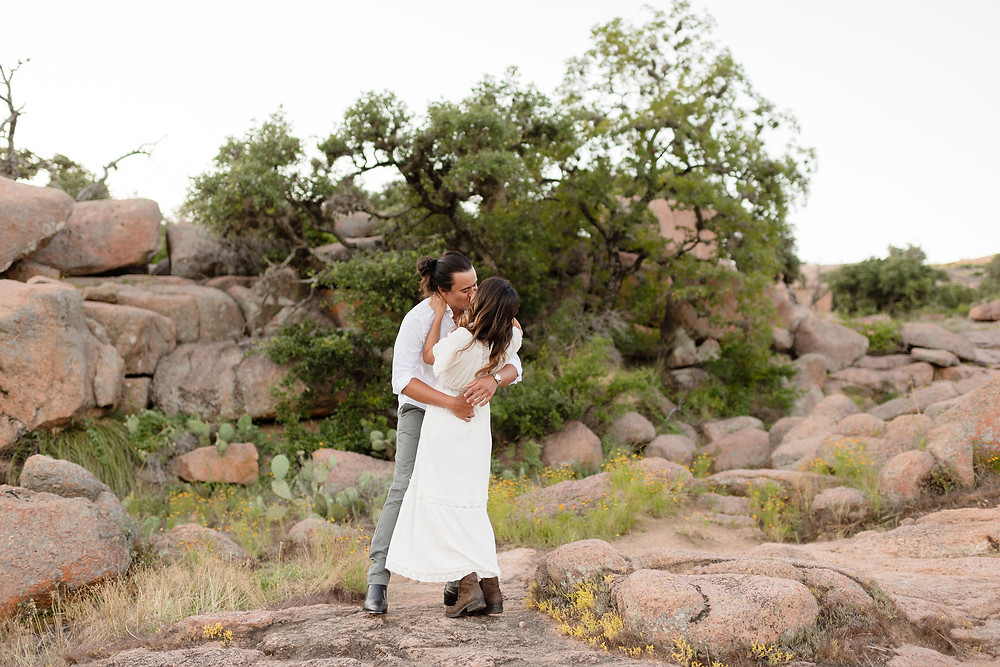 girl and guy with their arms wrapped around each other kissing. you can see rock formations behind them at enchanted rock state park