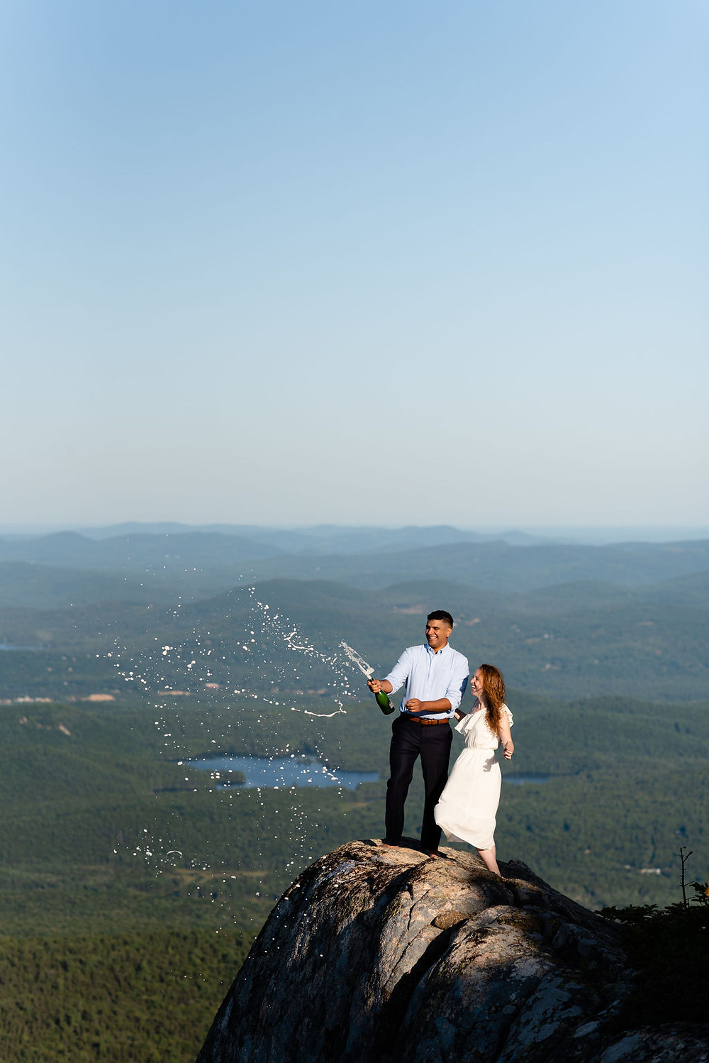 bride and groom on the summit of mount chocorua popping champagne for their elopement. New Hampshire elopement photographer