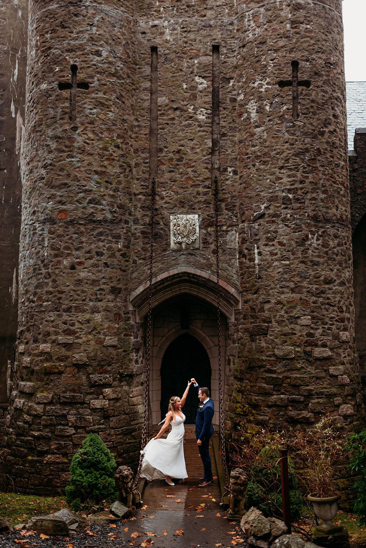 groom twirls bride on drawbridge out front of Hammond Castle Museum