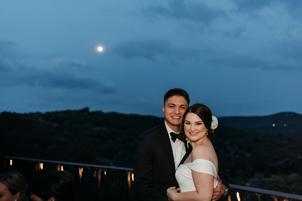 bride and groom pose after the sun sets with the moon in the background