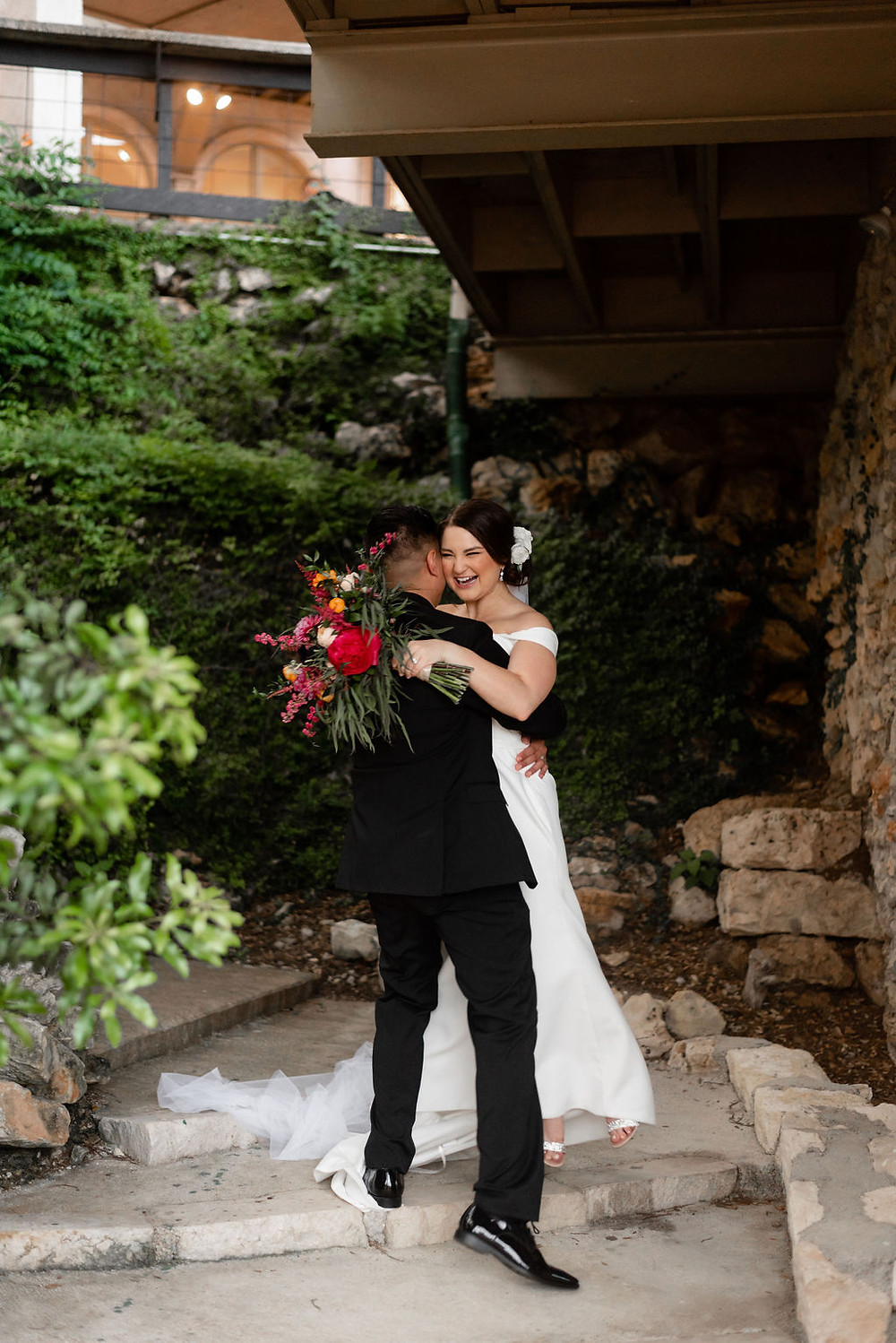 bride and groom walk through butterfly garden at villa antonia