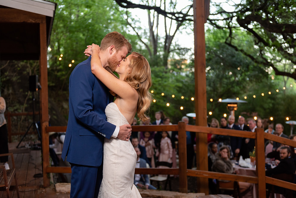 bride and groom first dance at wedding kissing