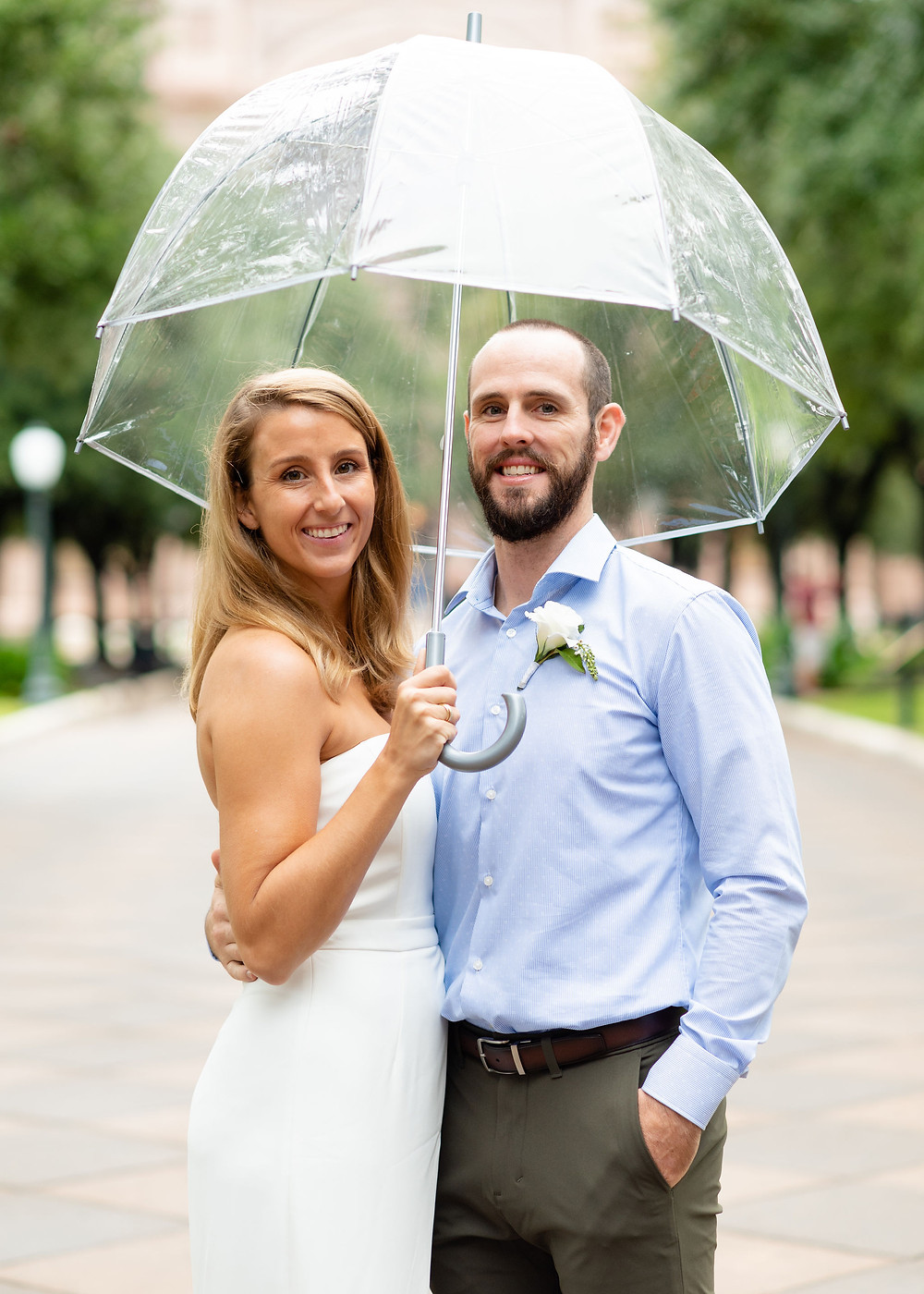 bride and groom in front of austin capitol building for elopement holding umbrella