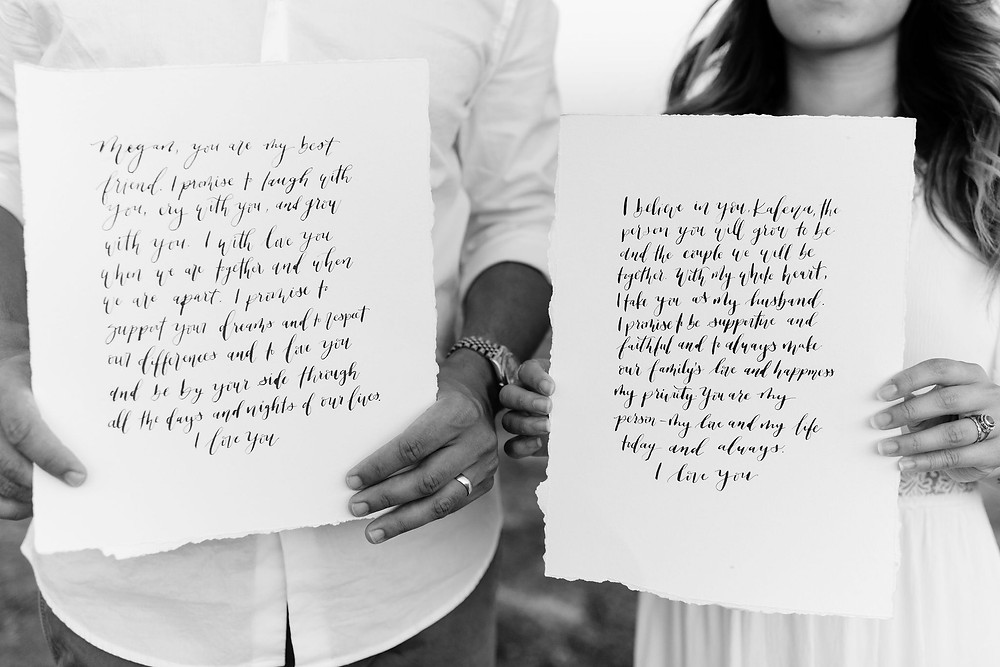 close up photo of a couple hand's presenting their vows to the camera