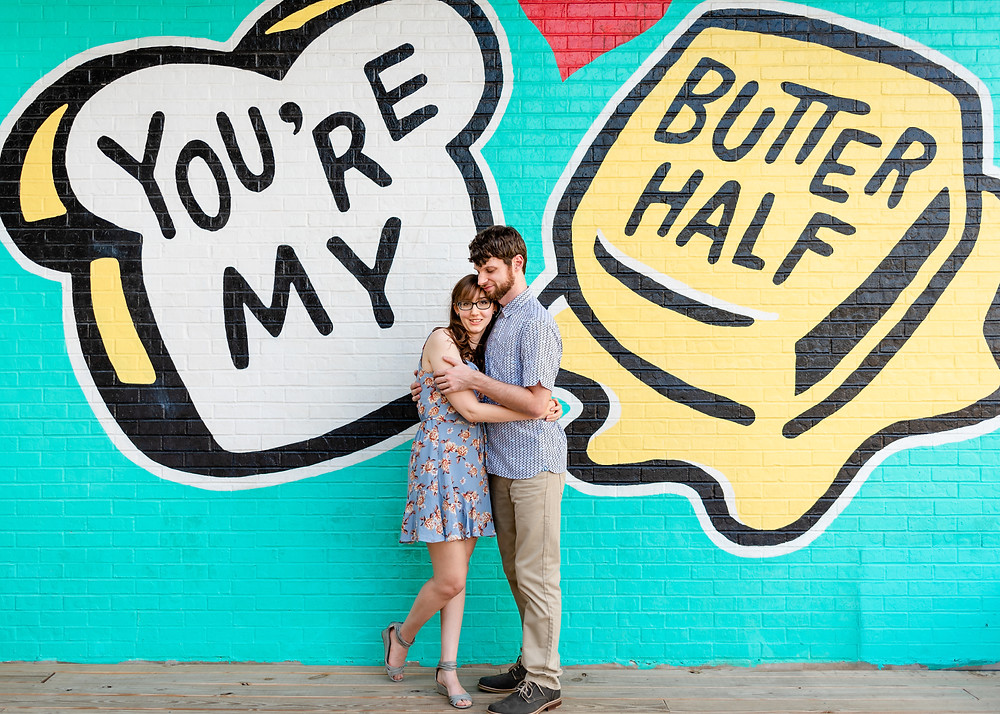 "Guy and girl are embracing in a hug. Girl is looking and smiling at the camera while the guy looks towards the girl. They're standing in front of the ""you're my butter half"" mural in austin for their engagement photos"