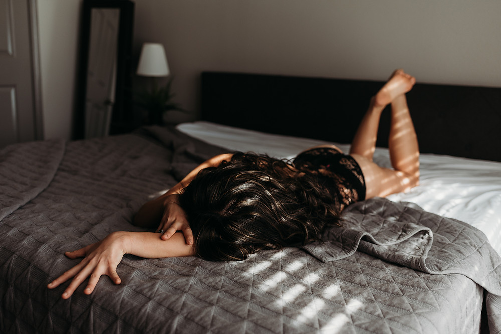 boudoir session on bed with direct shadow window light