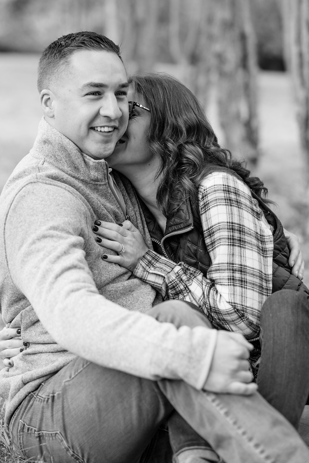 couple sits on ground for engagement photos. girl kisses guy's cheek