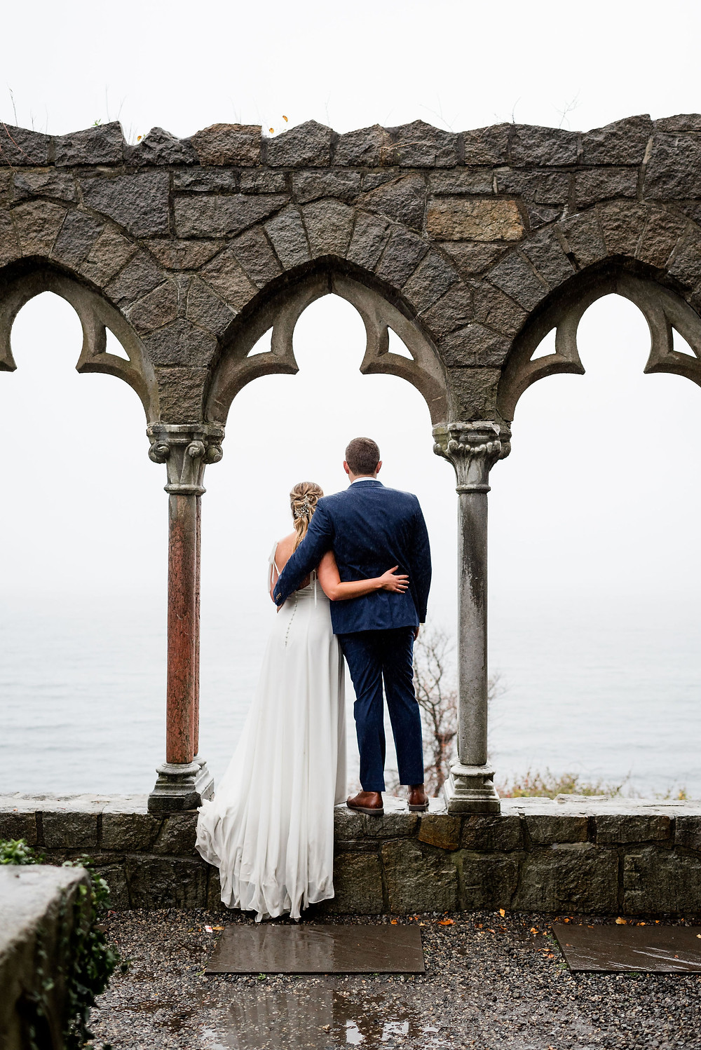 bride and groom standing in archway at hammond castle looking out at the atlantic ocean