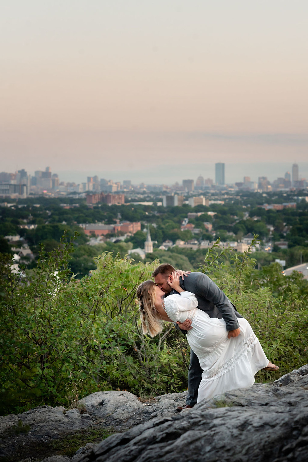 a couple doing a dip kiss during their elopement. you can see the boston skyline in the background