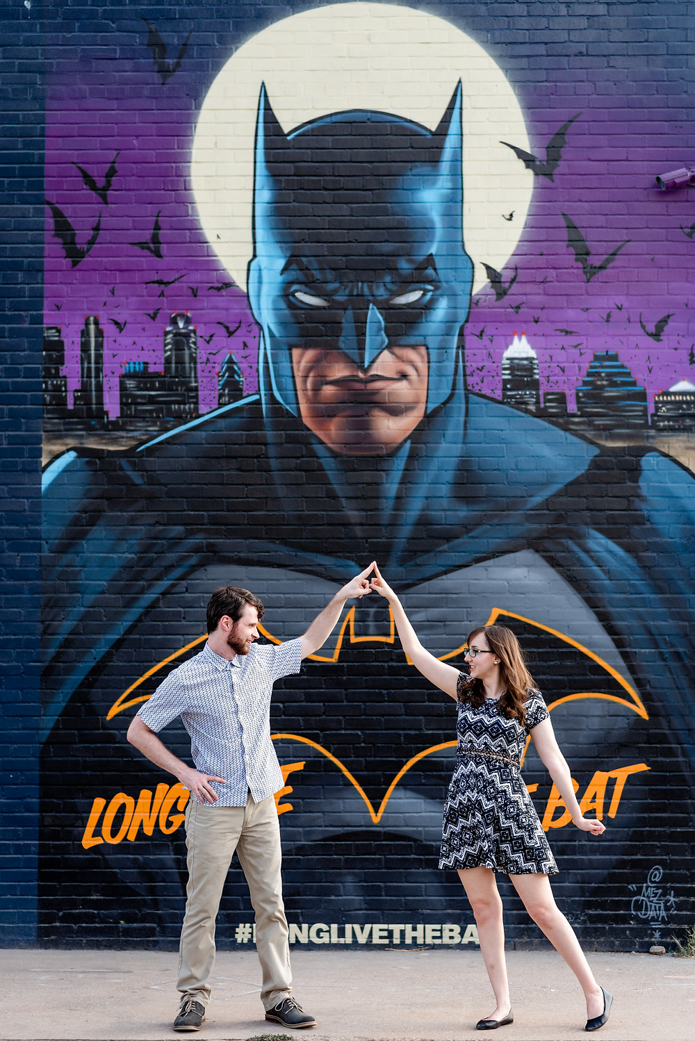 girl and guy stand in front of batman mural in austin for their engagement photos. They're standing next to each other, looking at each other with only their pointer fingers touching; in a pose that has to do with the comic books