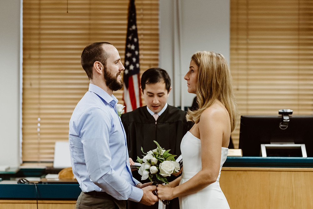bride and groom standing in front of Judge Chu during wedding ceremony at travis county courthouse