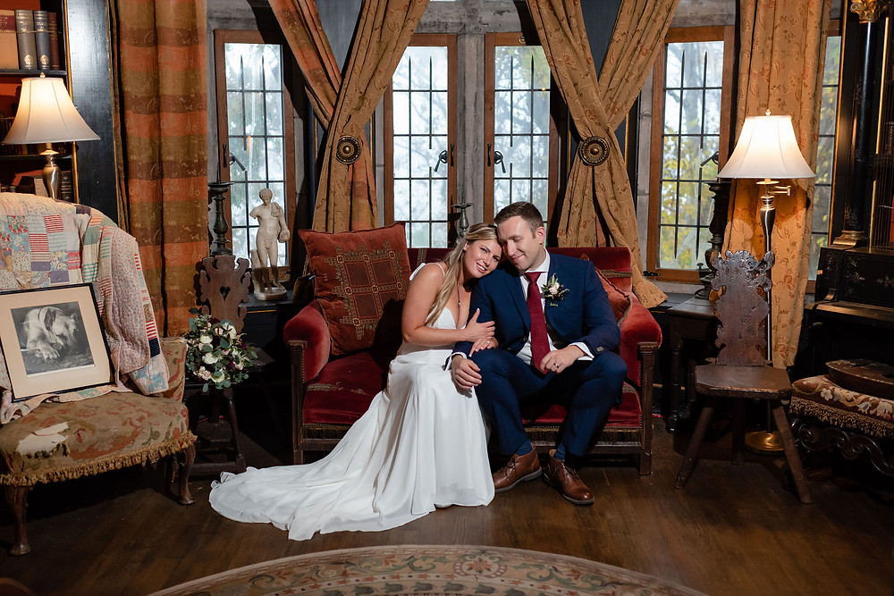 bride and groom sitting on velvet couch in library