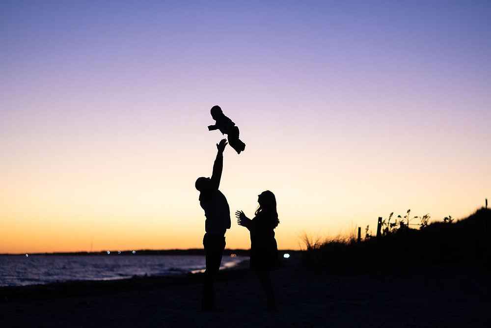 couple on beach for engagement photos at lighthouse inn in West Dennis Cape cod, MA during sunset. Photo is a silhouette of dad throwing baby in the air with the sunset behind them