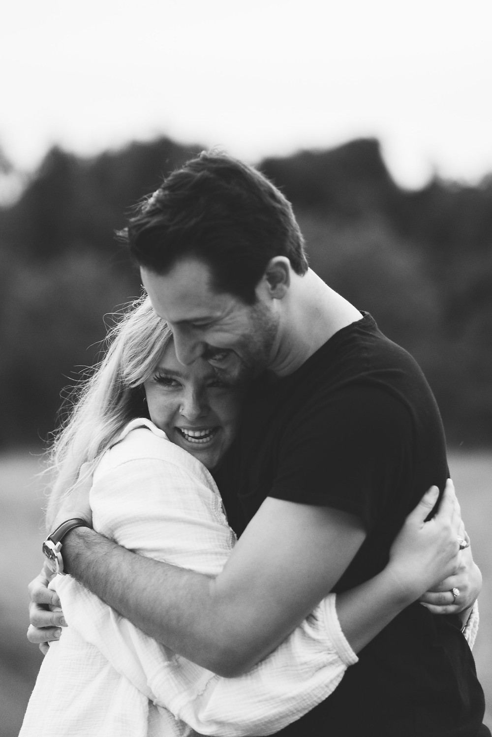 black and white photo of couple hugging after getting engaged