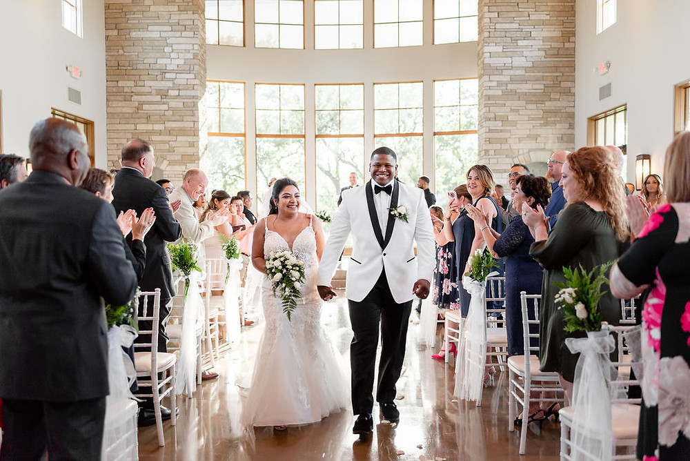 canyonwood ridge wedding ceremony area. photo is from the back of the aisle so you can see guests backs as they clap for the bride and groom walking down the aisle, towards the camera, after just getting married. Groom has. big smile and is looking at the camera. bride is looking at the guests.