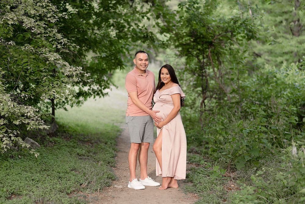 couple stands on a dirt path in the middle of greenery at a park. Both people have their hands on the pregnant belly. The girl is wearing a pink dress with a slit and she is standing so that her knee pokes out of the slit. They look at the camera smiling