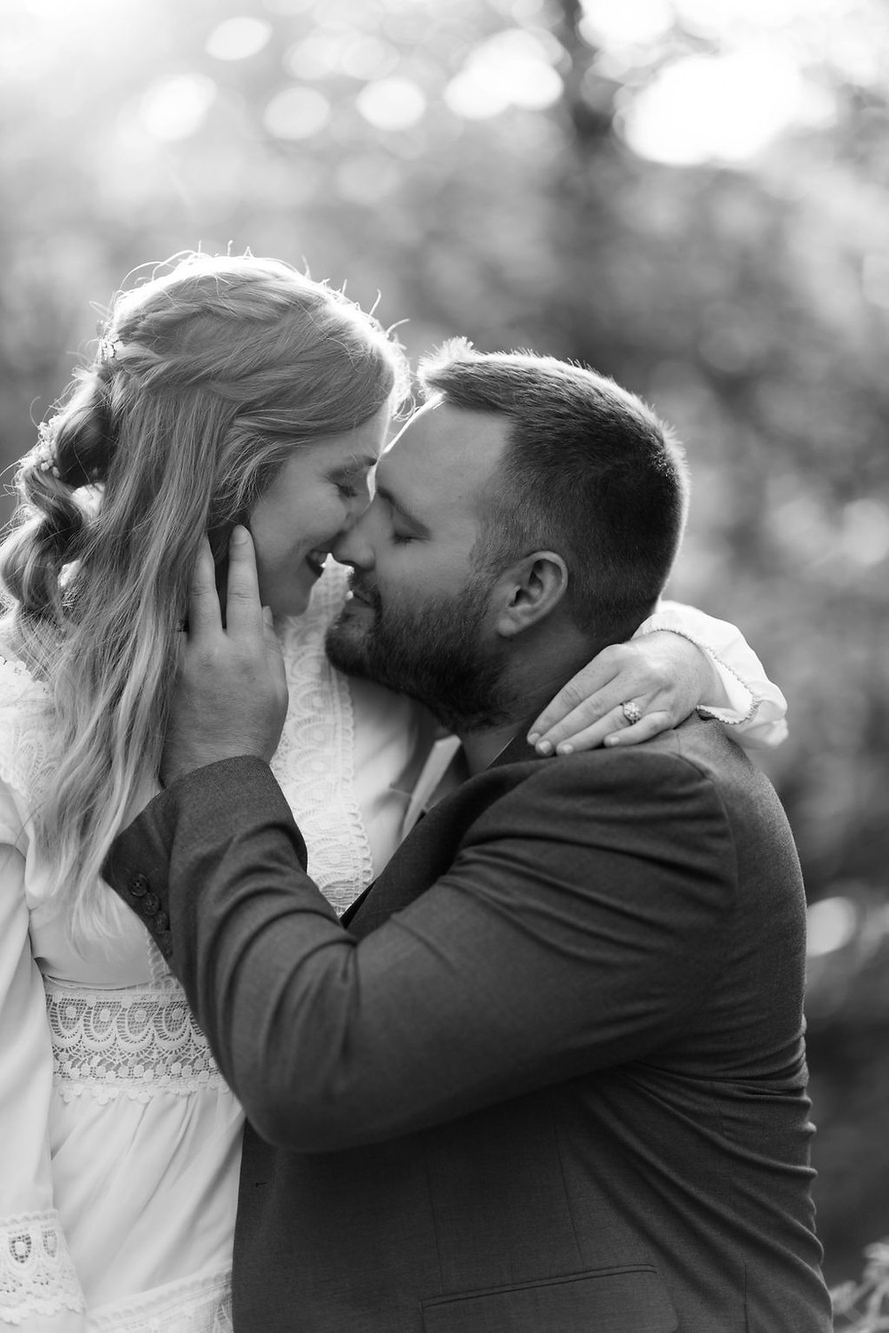 close up photo of a bride and groom with their foreheads together. they are about to kiss. the groom has his hand on the bride's face