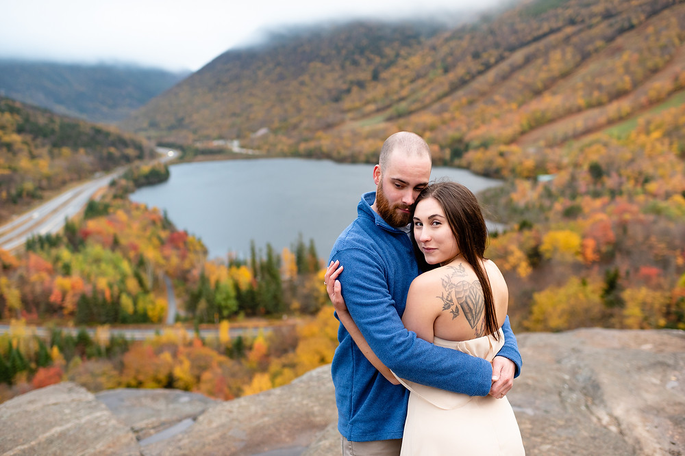 guy has arms wrapped around girl, face to face, with girl looking over her shoulder at the camera. fall foliage and echo lake behind them