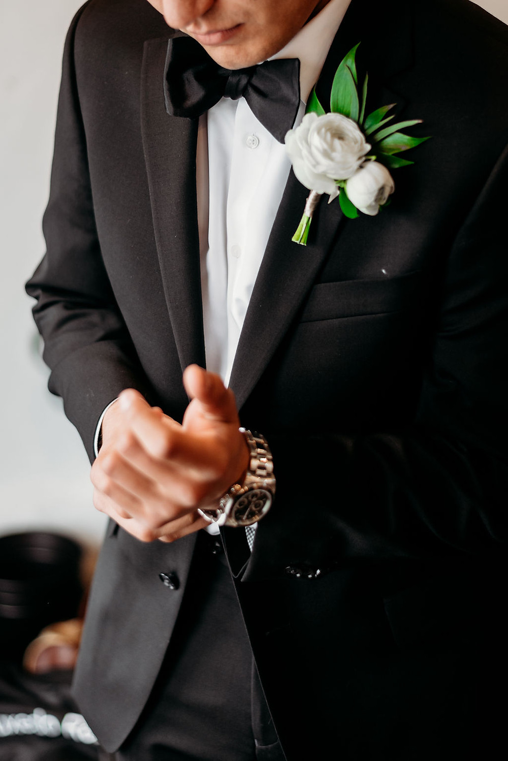 groom puts on watch. close up detail photo pre-wedding