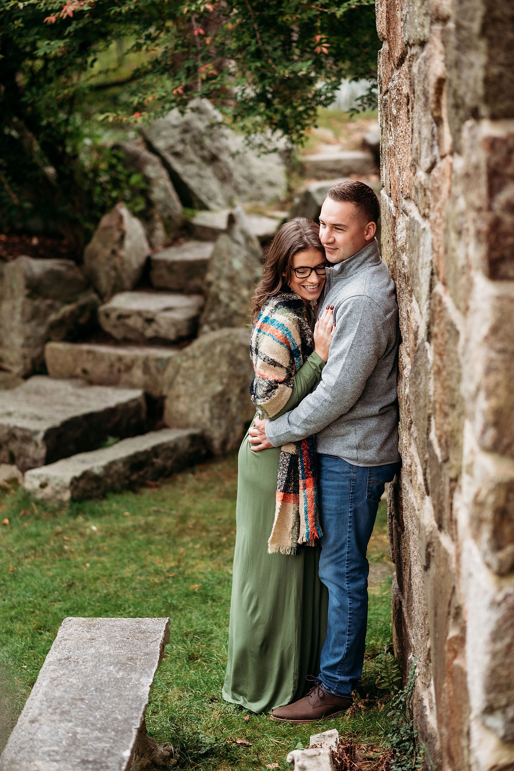 guy's back is against stone wall. girl is leaning on him so they are chest to chest. she's smiling big and looking at the ground. he is looking over her head