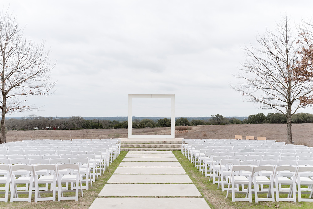 the ceremony area at prospect house. white chairs set up looking at the alter space. the alter has three steps to the top and then a large white square installation. it is just an outline of a square so that you can see through the middle to the field beyond
