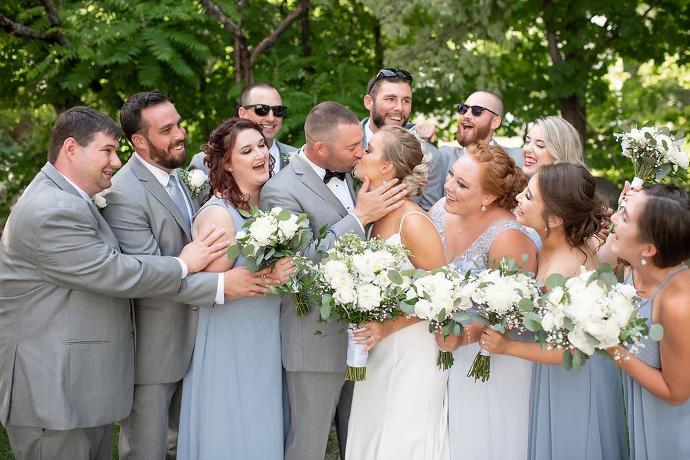 fun wedding party picture everyone laughing while bride and groom kiss