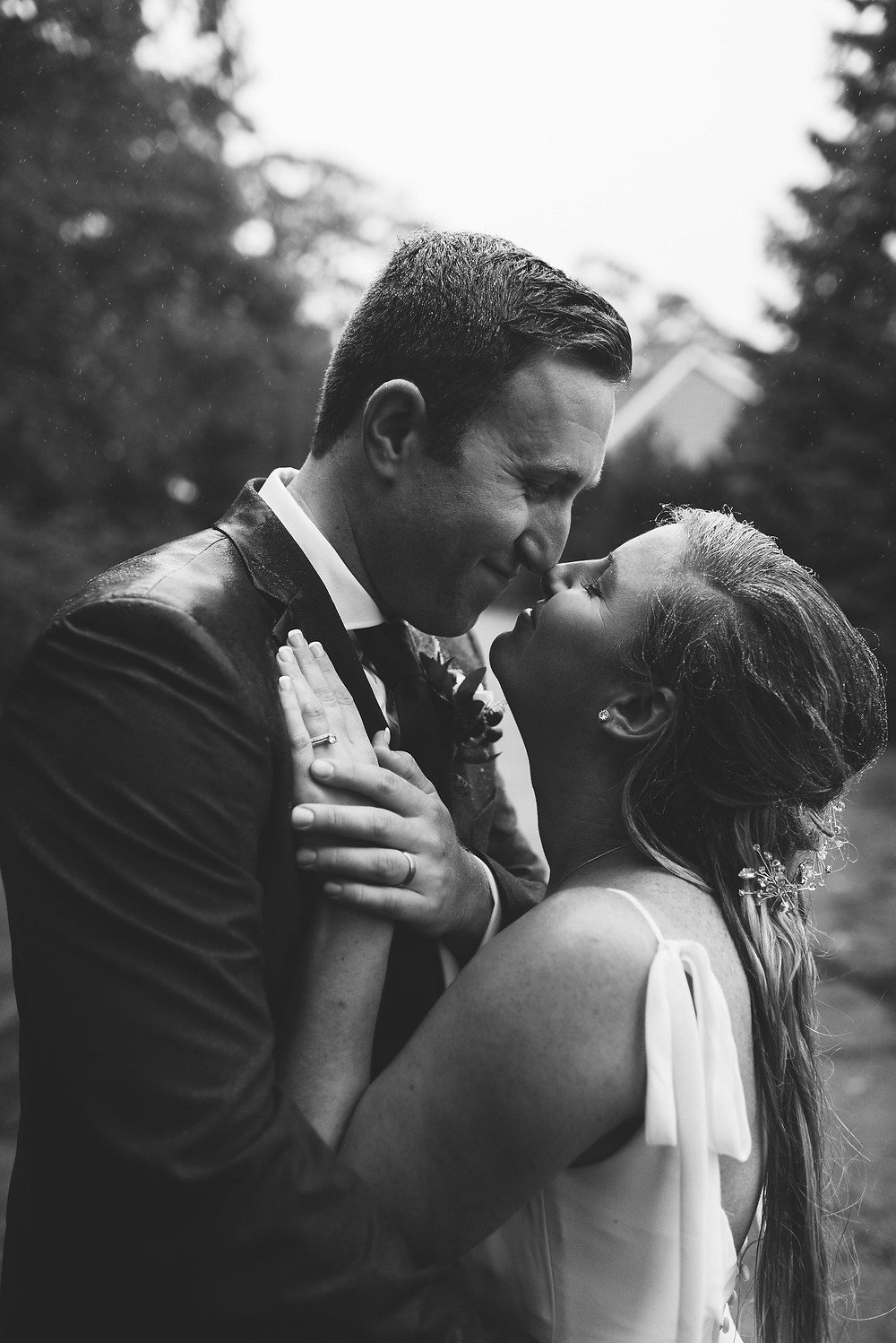 black and white photo of groom and bride almost kissing. you can tell it's raining