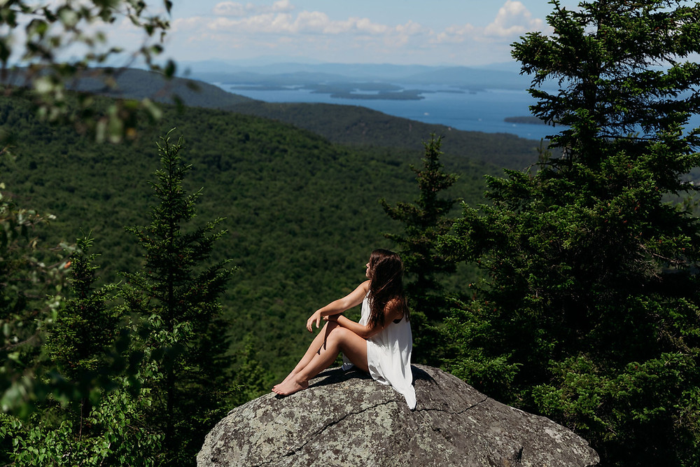 view from mount major. in frame is a girl with a white dress between trees. you can see new hampshire lakes in the background