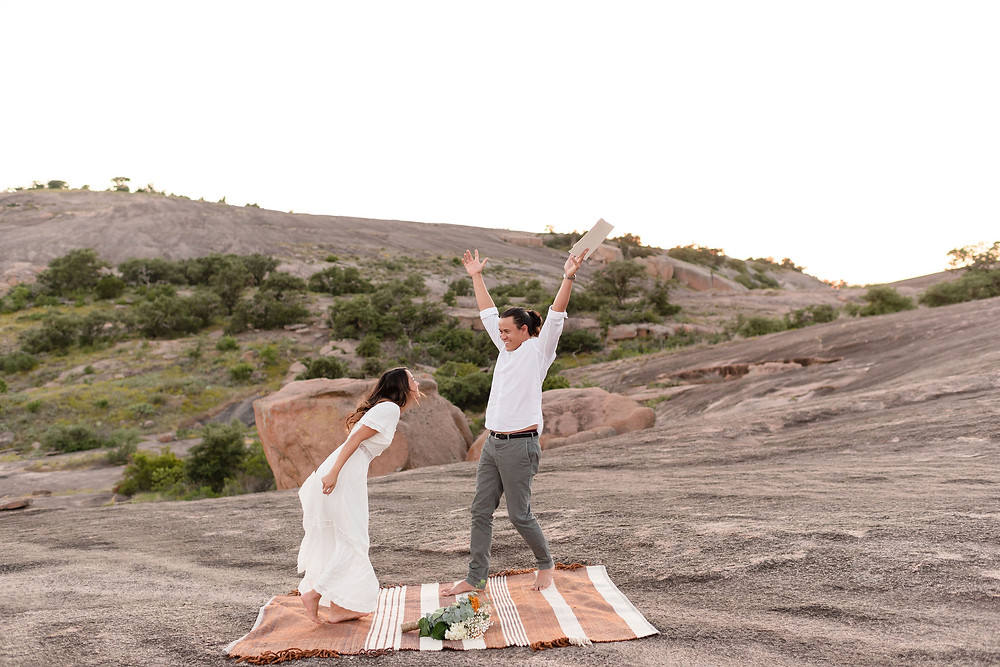 """couple with their arms in the air celebrating after they say """"i do"""""""