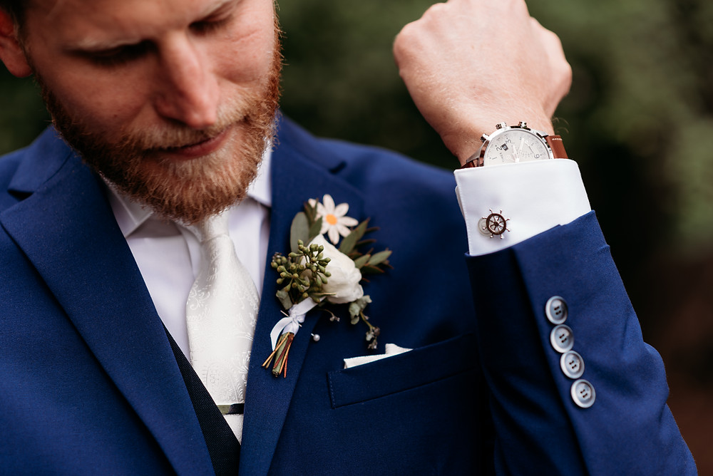 groom showing off his cuff links and watch