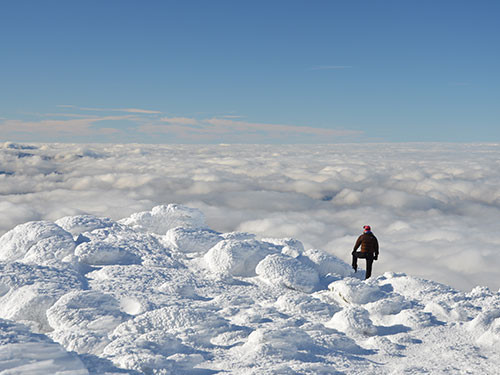 snowy mount washington summit. hiker above the clouds