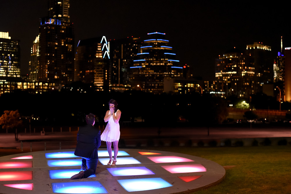 man down on one knee proposing to girlfriend on the checkerboard ground lights at the long center at night with the austin skyline lit up behind them