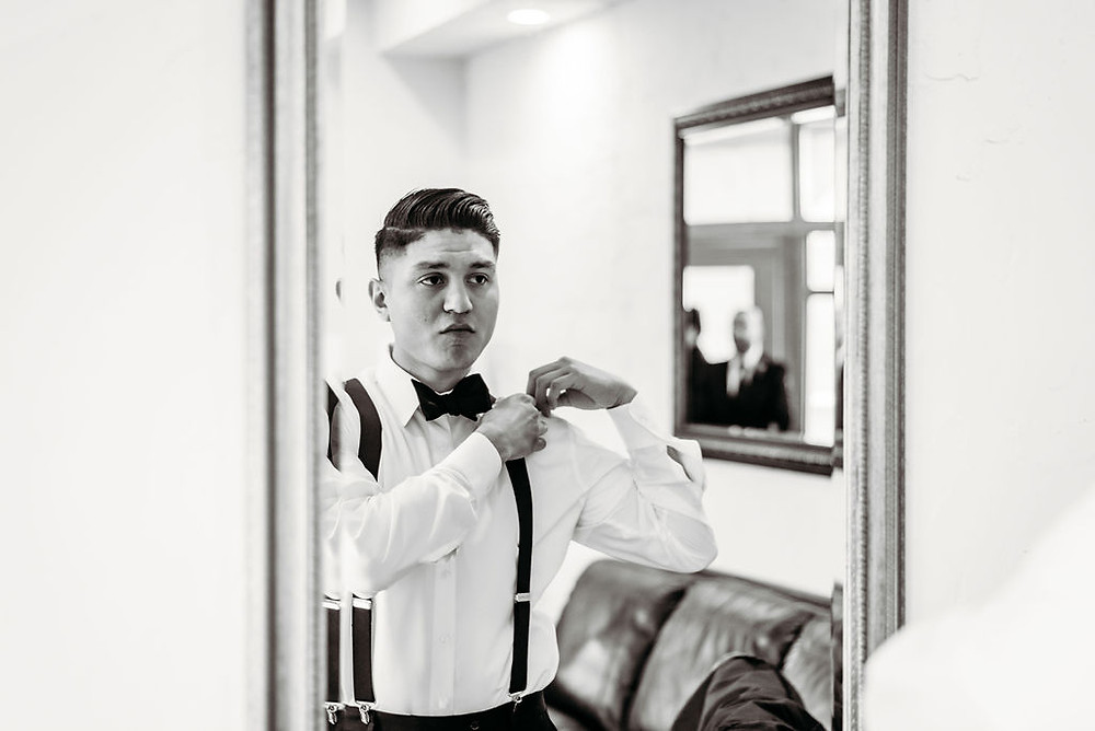 groom looks in mirror to put on suspenders getting ready for wedding at villa antonia