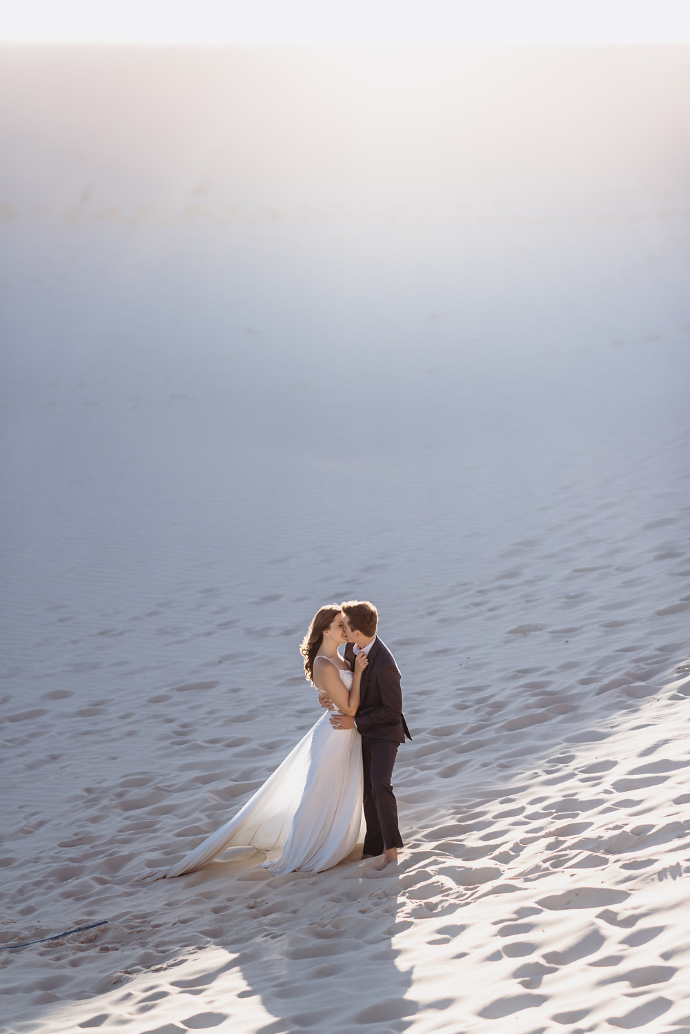 couple has their arms wrapped around each other during their elopement ceremony. They are sharing their first kiss. the sun light creeps over the sandhills in the background creating a soft, ethereal like glow