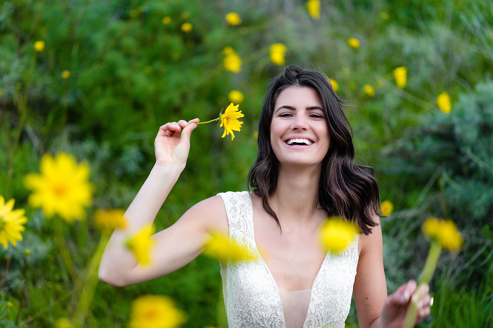 bride laughing with yellow wild flowers