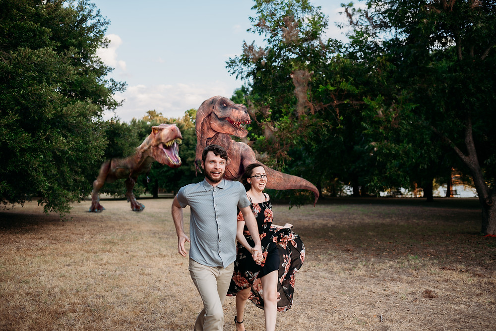 couple runs away from dinosaurs which were added in photoshop