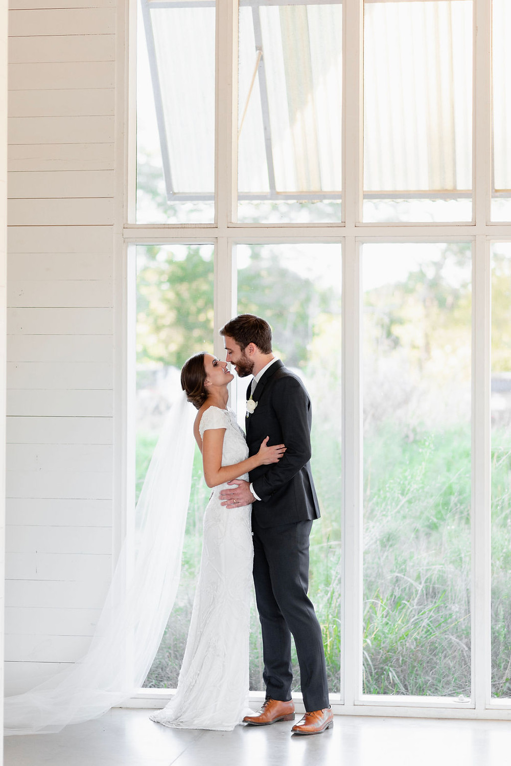 bride and groom posing with their faces almost touching in front of tall windows. beautiful natural light