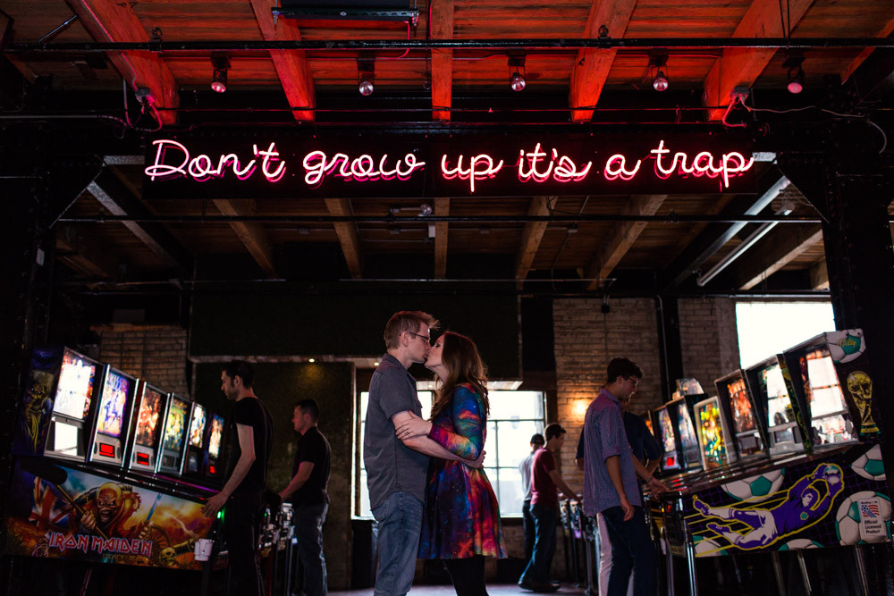 "couple kiss in an arcade with the words ""don't grow up it's a trap"" above them in neon lights"