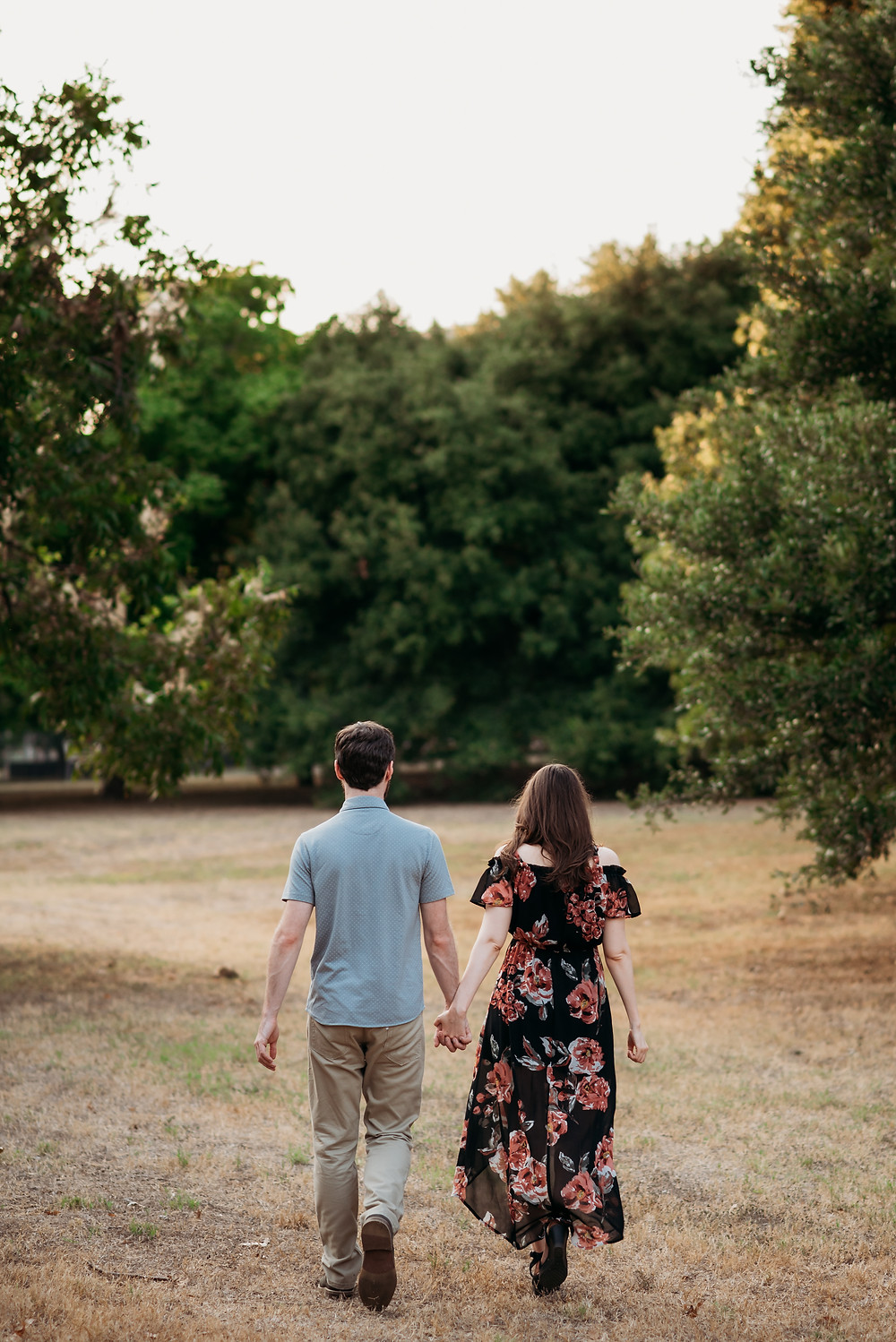 couple is holding hands walking away from the camera in a field