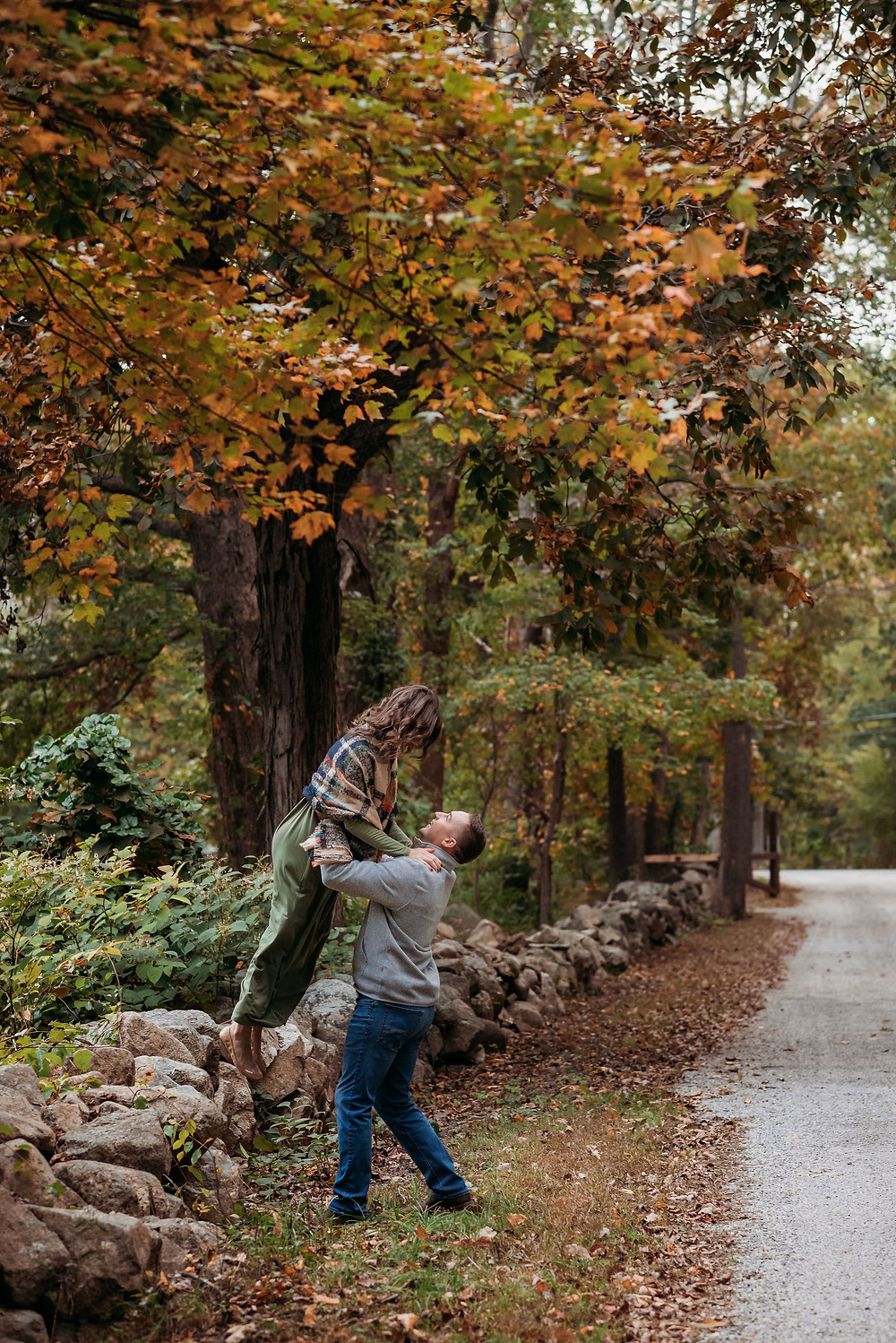 guy helps girl hop off of a rock wall on the side of the road. there is lots of fall foliage surrounding them