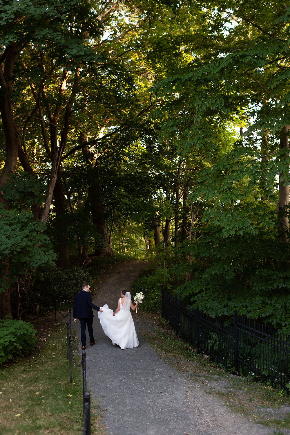 couple walking down path at Tupper Manor through the woods to get to the beach