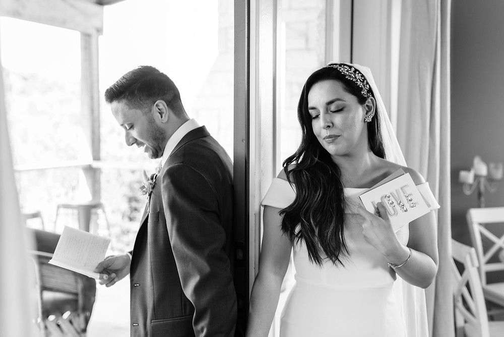 bride and groom stand on each side of a closed door holding hands for their no look first look before their wedding. you can see the bride mostly. she has her eyes closed, listening to the groom read a letter to her