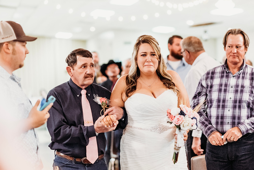 bride crying while walking down aisle with her father