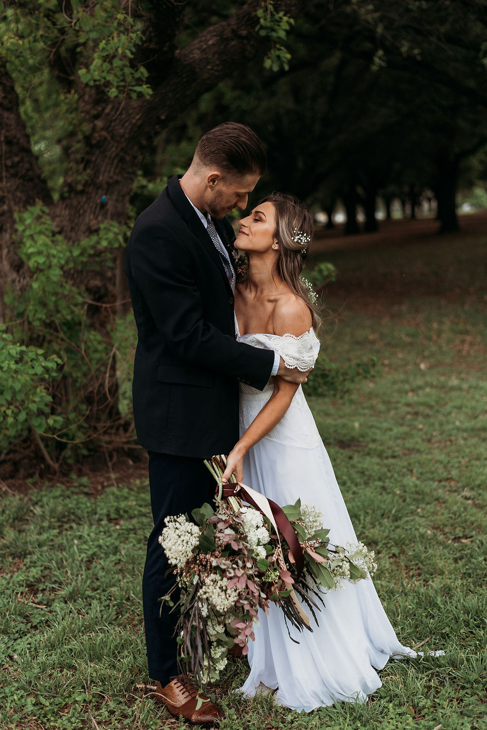bride and groom poses. Groom looks down at bride who has her eyes closed and her dress is slipping off her shoulder. romantic newlywed photo where you can feel the love during their austin elopement